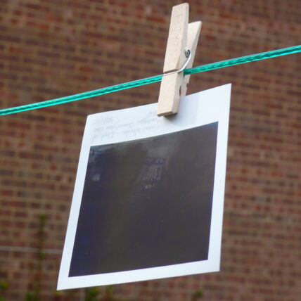 Obscured polaroid photo hung on a clothesline with a pin