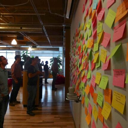 wall of post-it notes with people looking at it