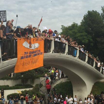 People protesting with flags and banners on a bridge