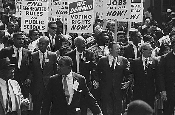 Civil rights era protest with men in suits holding hands and picket signs