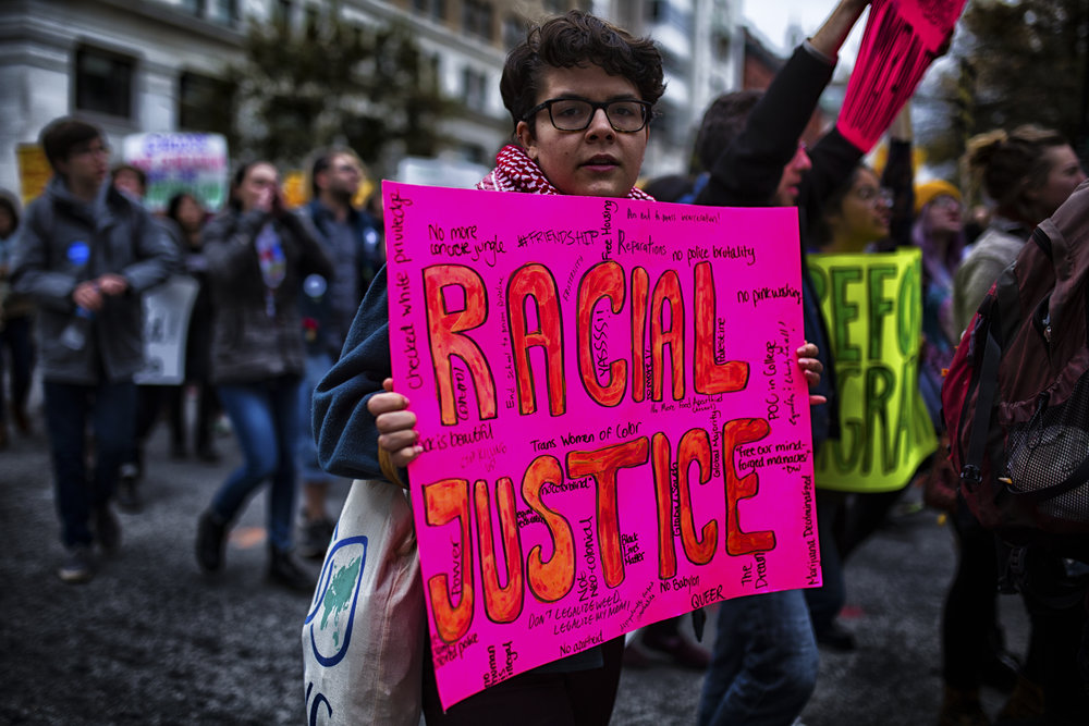 Person holding racial justice sign