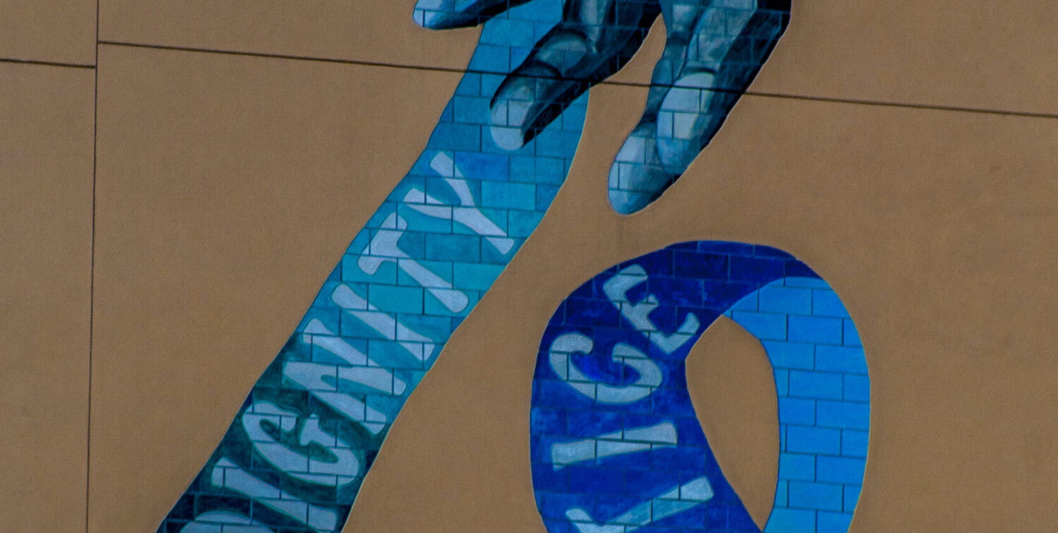 mural of hand and text of justice, dignity, love on blue ribbon