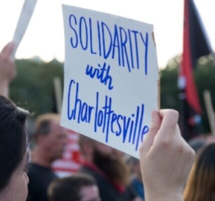 A protester holding a sign that reads solidarity with Charlottesville