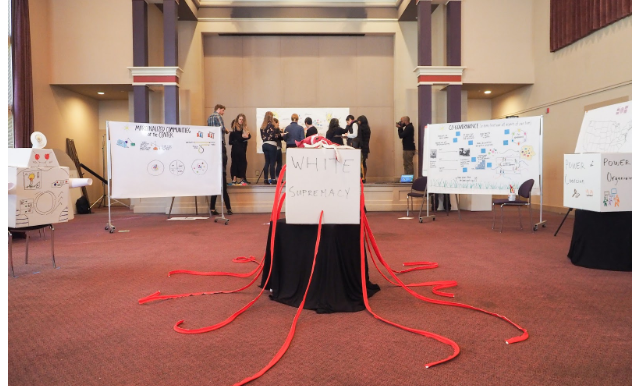 Photograph of convening in a ballroom with interactive components and whiteboards