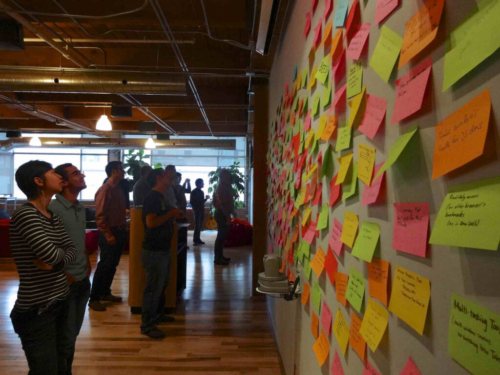 people looking at a wall with post-it nots