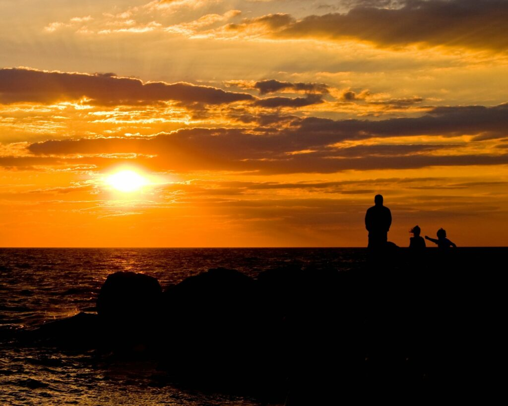 Silhouettes of three people watching a sunset over water