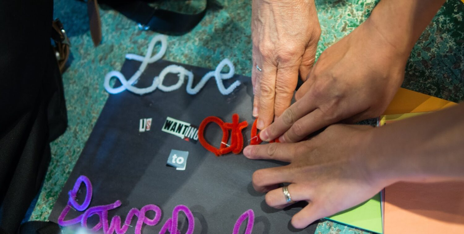 """Photo of hands touching piece that reads """"love is powerful"""""""