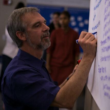 Mark Leach in a blue shirt writes on a whiteboard