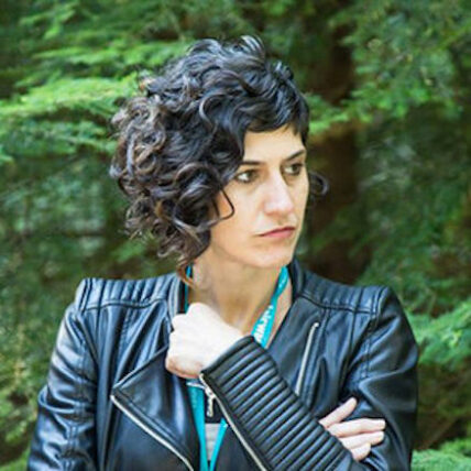 Photo of Mariana Ruiz Kairos in three quarter profile, hair short and wavy, wearing a leather jacket, arms crossed