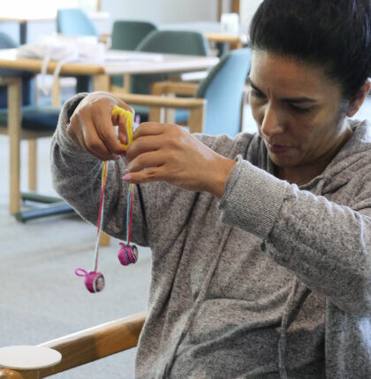 Photo of person wearing grey sweatshirt with hanging spools of thread in their hands