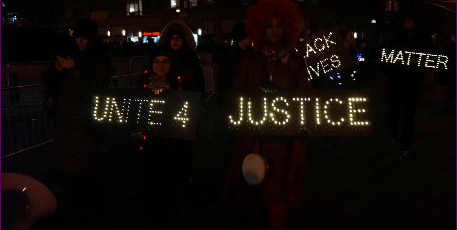 Photo of Black Live Matter nighttime protest, slogans glowing
