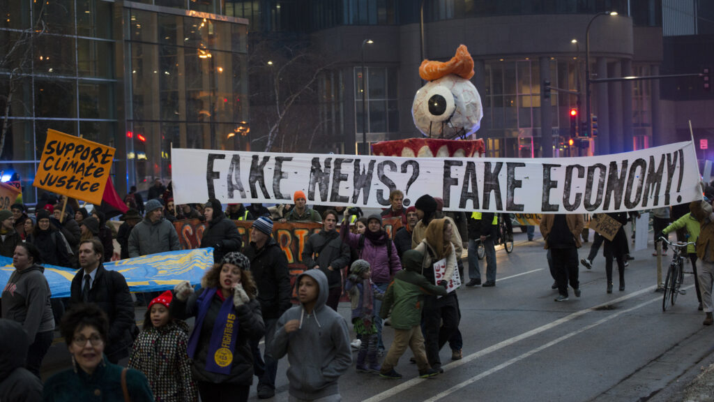 "Protest with big banner that says ""fake news? fake economy!"" and an artistic float"