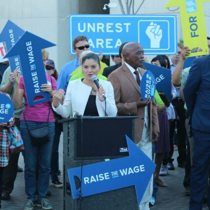 """Person speaks at a podium at a """"raise the wage"""" protest"""
